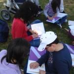 bambini e operatrici che leggono libri tattili su un prato